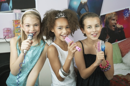 slumber party: Girls using brushes microphones to sing at a Slumber Party LANG_EVOIMAGES
