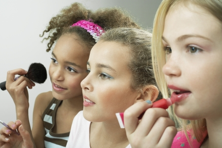 beautiful preteen girl: Girls standing side by side putting on make-up and lip gloss