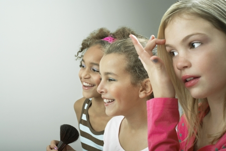 beautiful preteen girl: Girls standing side by side putting on make-up fixing hair