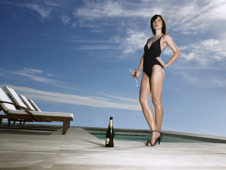 one piece swimsuit: Woman in bathing suit holding champagne at poolside