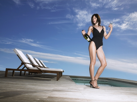 decadence: Woman in bathing suit holding champagne at poolside