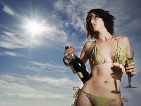 alcohol bottles: Woman in bikini holding champagne outdoors LANG_EVOIMAGES