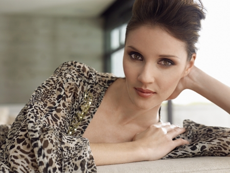 leopard print: Young woman leaning on elbow indoors close-up portrait LANG_EVOIMAGES