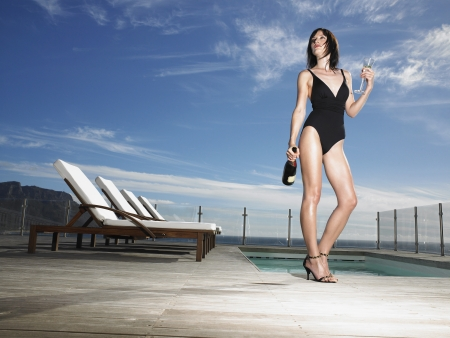 alcohol bottles: Woman in bathing suit standing with champagne at outdoor pool