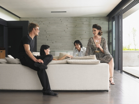 small room: Young people drinking champagne in living room LANG_EVOIMAGES