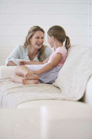 knees bent: Mother crouching next to girl sitting on sofa LANG_EVOIMAGES