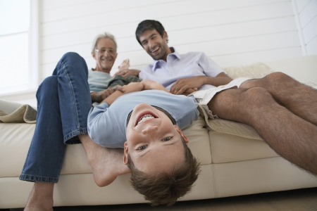 Boy hanging upside down off couch with father and grandfather sitting beside him Stock Photo - 18898614