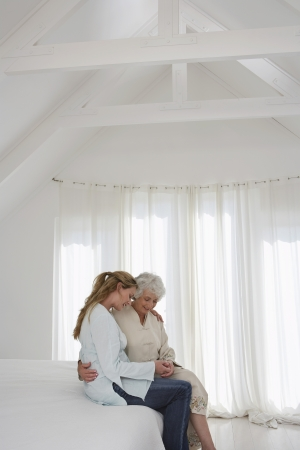 Mother and adult daughter sitting on bed in bedroom Stock Photo - 18898639