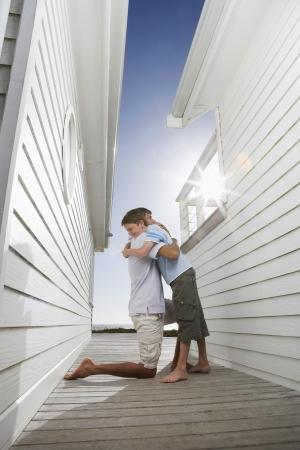 passageway: Father hugging son in passageway between buildings side view