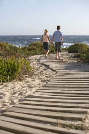 Boy and girl walking hand in hand along boardwalk toward sea back view Stock Photo