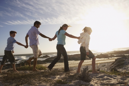 Parents and children walking hand in hand on seashore side view Stock Photo - 18898658