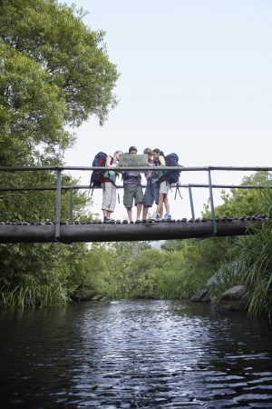ecotourism: Four teenagers (16-17 years) backpacking in forest reading map on bridge LANG_EVOIMAGES