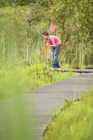 preadolescence: Boy Looking for Wildlife in Marsh LANG_EVOIMAGES