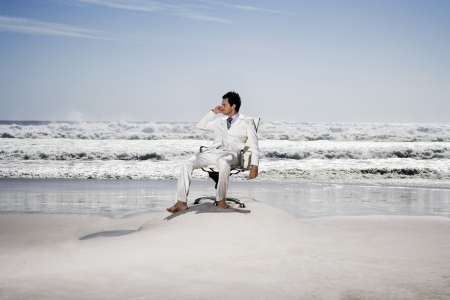 Man using mobile phone sitting on office chair on beach Stock Photo - 18898735