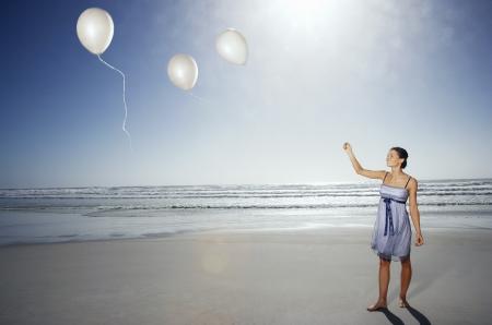 Vrouw laten ballonnen gaan op strand opgeheven mening Stockfoto
