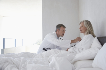 house call: Doctor doing house call on mature woman in bed using stethoscope side view