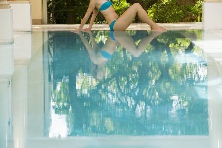 low section: Young woman sitting by swimming pool side view low section