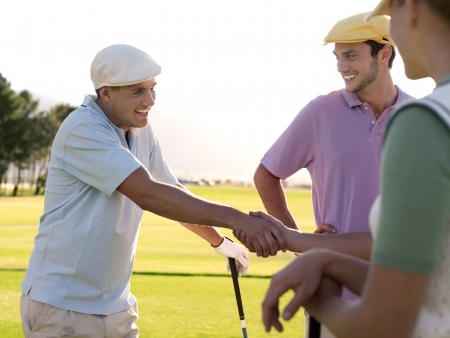 arm extended: Yong golfers shaking hands on course LANG_EVOIMAGES