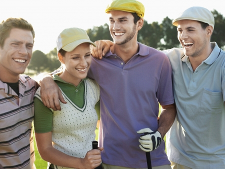 golf cap: Smiling group young golfers with arms around each others shoulders on golf course LANG_EVOIMAGES