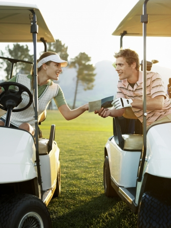 golf cart: Young golfers sitting in golf cart holding score card