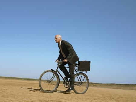 daremny: Businessman riding bicycle in desert LANG_EVOIMAGES