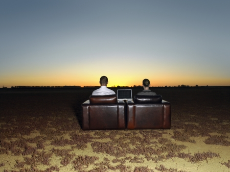 arm chairs: Two business people in arm chairs in open plain at sunset back view LANG_EVOIMAGES