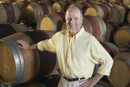 casks: Man leaning on wine casks