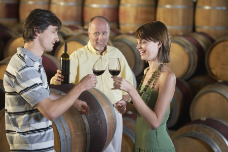 wine tasting: Three people wine-tasting beside wine casks