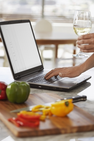 unknown age: Man using lap top and chopping peppers in kitchen close up of hands