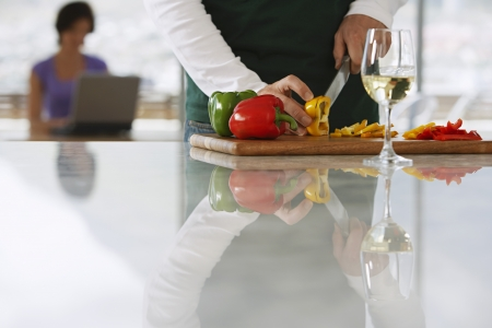 Man (mid section) chopping peppers in front of woman on lap top in kitchen focus on foreground