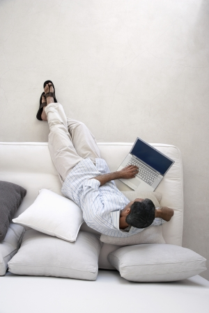 Man using laptop sitting on sofa in living room view from above Stock Photo - 18899117