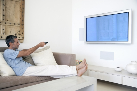 greying: Man using remote control reclining on couch in living room side view