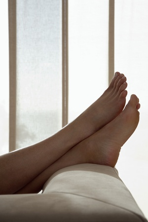 Woman resting with feet up on sofa in living room close up of feet low section Stock Photo - 18899140