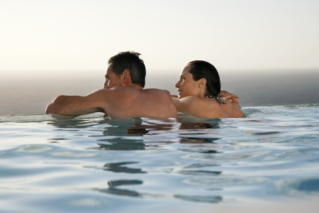 pool side: Couple relaxing in infinity pool at sunset back view