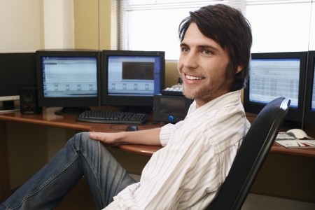 Man sitting at desk in front of computers.