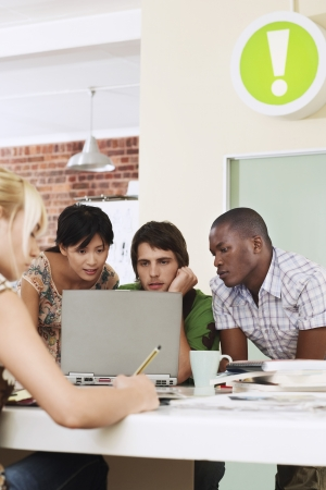четыре человека: Четыре людей, имеющих совещание вокруг ноутбука. LANG_EVOIMAGES