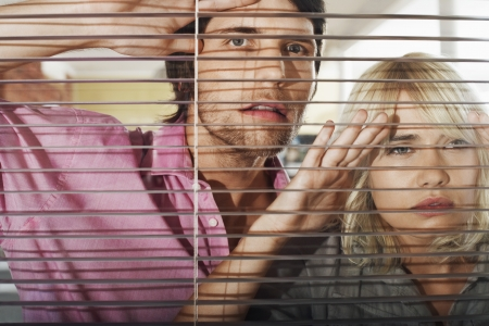 blind people: Young woman and man looking through Venetian Blinds front view.