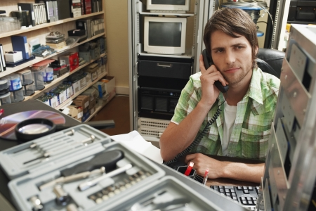 Man using phone surrounded by computer equipment Stock Photo - 18899194