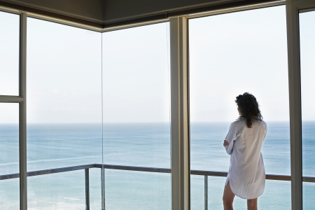 view window: Woman looking at view standing on balcony back view LANG_EVOIMAGES