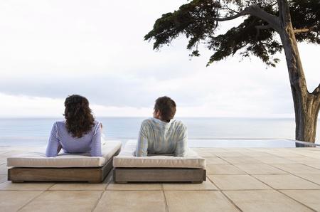 mujer mirando el horizonte: Pares que descansan en las tumbonas de piscina mirando al mar Vista posterior LANG_EVOIMAGES