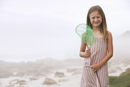 beach butterfly: Girl at Rocky Beach Holding Butterfly Net