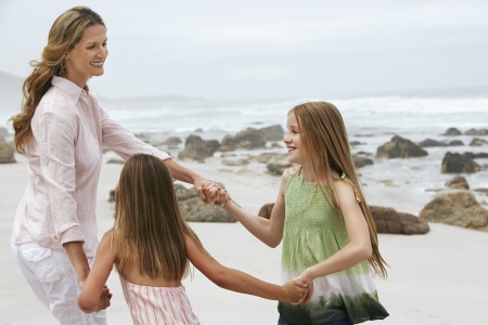 early 40s: Mother with Two Girls Playing on Beach LANG_EVOIMAGES