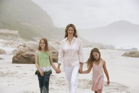 going nowhere: Mother Walking Hand in Hand with Two Girls on Beach