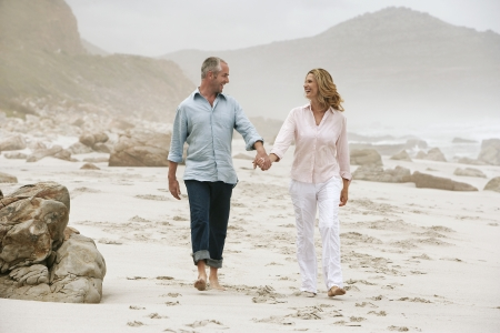 vacationing: Couple Strolling Hand in Hand on Beach