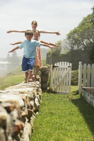 Three Children Balancing on Wall