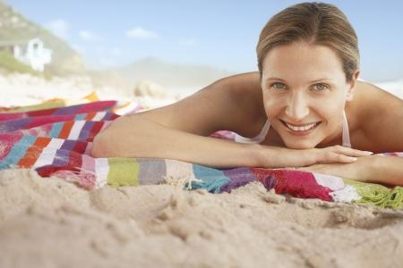 early 40s: Woman Sunbathing on Beach