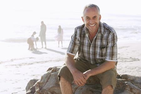 hombre sentado: Padre con la familia en la playa