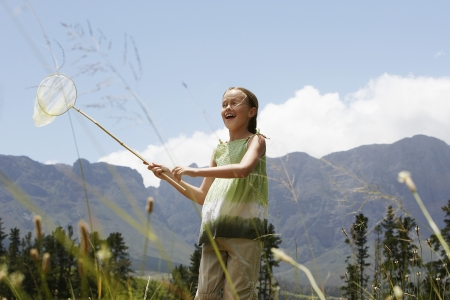 butterfly net: Girl (7-9) standing in field holding butterfly net low angle view