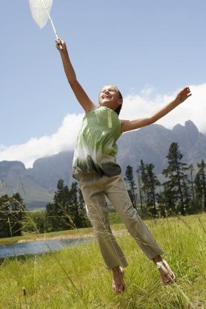 butterfly net: Girl (7-9) in field reaching towards sky with butterfly net.
