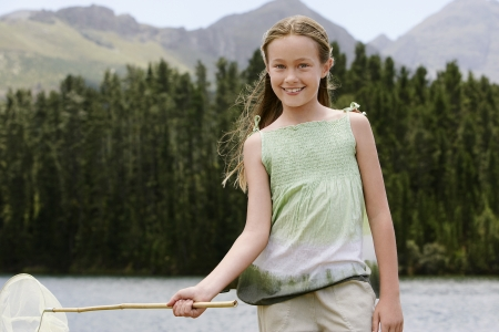 butterfly net: Girl (7-9) standing outdoors by lake holding butterfly net front view portrait